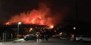 People stand in a parking lot at night, looking at a mountainside glowing with orange fire and smoke.