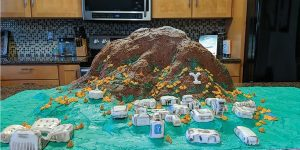 A model of BYU campus, complete with Y Mountain, made from rice crispy treats are displayed on a green table cloth.