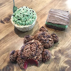 Three treats molded from rice crispy treats sit on a table: a large chocolate cinnamon bear, a BYU mint brownie, and a cup of ice cream.