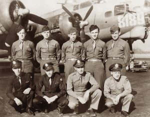 A sepia photo of nine men in military uniforms posing in front of a WWII airplane.