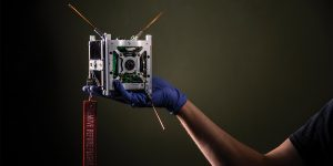 A CubeSat—a small satellite that looks like a metal cube—being held by a hand.