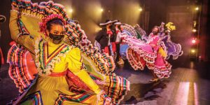 Male and female dancers wearing colorful traditional Central American costumes perform on stage.