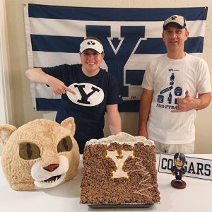 Two BYU fans stand in front of a BYU flag. They point to the table in front of them, which displays a Y Mountain replica made from rice crispy treats. The Y on the mountain is illuminated.