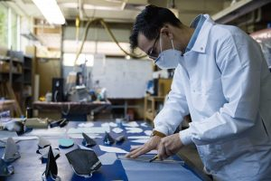 A male student in a white lab coat, wearing a mask, cuts fabric with a small blade to make cloth masks.