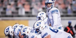 BYU quarterback stands behind the offensive line.