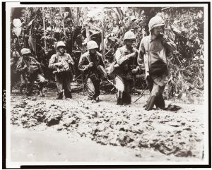 A sepia photo from 1943 shows US marines marching through mud on Bougainville Island, Solomon Islands.