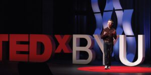 Dave Vance stands on the red TEDxBYU stage, gesturing emphatically to his audience.