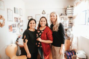 Three women, the founders of Yapay Bolivia, pose for a photo together in someone's home.