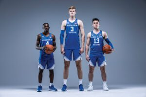 BYU men's basketball starters Brandon Averette, Matt Haarms, and Alex Barcello stand in front of a gray backdrop.