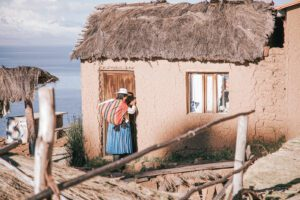 A woman carrying a colorful sack over her shoulder knocks on a traditional Bolivian home.