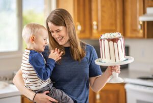 A young mom holds her toddler son in one arm and a beautifully decorated cake in the other.