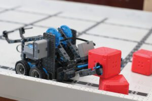 A tiny robot made of plastic parts picks up a small red block.