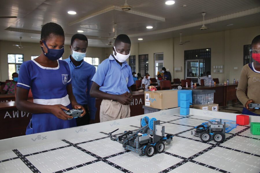 A group of Ghanian school children operate small robotic cars.