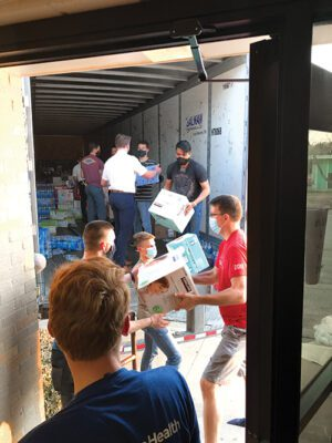 Several volunteers and a missionary unload boxes of supplies from a moving truck.