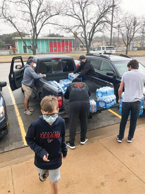 Five volunteers unload cases of water bottles from the back of a pickup truck.