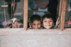 Three smiling Bolivian children look at the camera through a window.