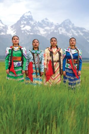 Four Native American women stand in traditional clothing in front of the Grand Teton mountains.