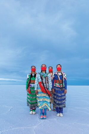 Four Native American young women in traditional clothing stand of the Great Salt Lake Salt Flats.