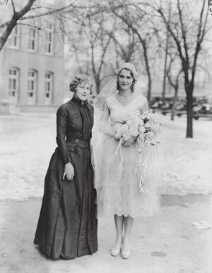 Two girls stand outside of the Training Building in the 1920s wearing handmade dresses.