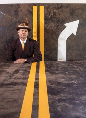 Artist Todd Stilson, wearing an orange tie and feathered top hat, stands in front of his road-inspired artwork. A table, also painted to look like a road, covers the bottom half of his body.