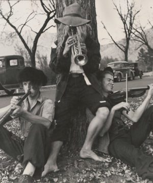 A black and white photo from the 1940s of three BYU students dressed up in hobo costumes and playing instruments.